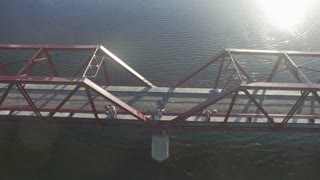 Aerial of Man Diving off Abandoned Red Bridge