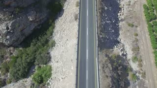 Flying Over Car Driving Through Mountain Road Tunnel Aerial Shot