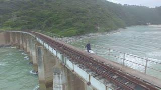 Girl Walking Across Ocean Bridge Aerial Revolving Shot
