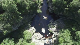 Man Floating in an Incredible River Forest Canyon Aerial Rising Shot