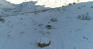 Aerial of Car Driving On Snow Covered Road