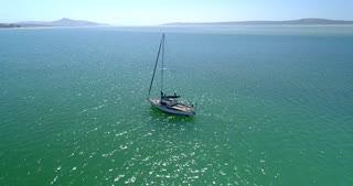 Aerial of Single Sailboat Floating in Crystal Blue Waters in South Africa