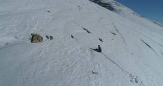 Aerial of Snowboarder Climbing Isolated Mountain Peak