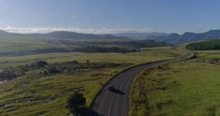 Following Car along Long Windy Road Towards Mountains and Forests Aerial View