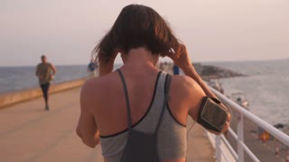 Active woman with smartphone running and listening to music