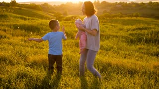 Adorable family having fun outdoors while dancing in field