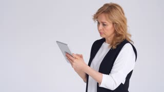 Adult Caucasian businesswoman using tablet