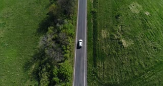 Aerial view white car driving on countryside road