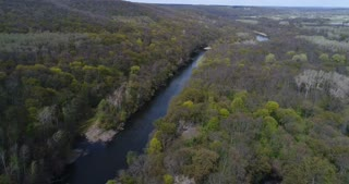 Arial flight over river flowing through spring forest