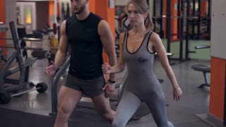 Athlete woman with personal trainer doing squats