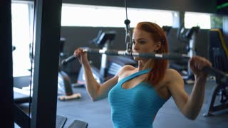 Athletic fitness woman flexing muscles on gym machine