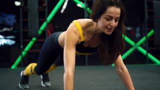 Athletic girl doing spiderman plank crunch