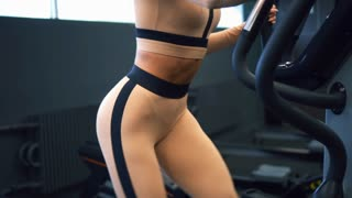 Athletic woman exercising on elliptical trainer