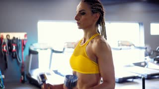 Attractive girl working out with dumbbells