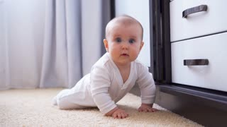 Baby crawling on the floor towards camera