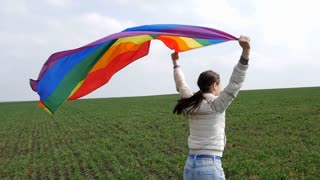 Back view of a woman running with LGBT flag