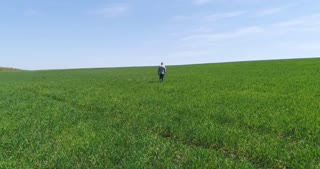 Back view of man marching on green field