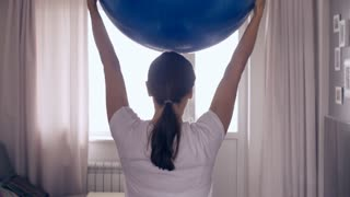 Back view of pregnant woman doing exercises with gymnastic ball