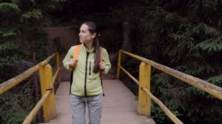 Backpacker woman crossing wooden bridge