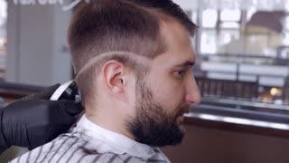 Barber in black gloves doing haircut for bearded man
