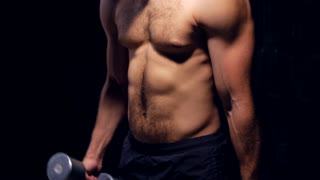 Bare-chested male athlete with dumbbells pumping up biceps