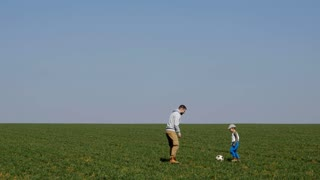 Bearded father and son practicing football, panning