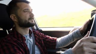 Bearded man driving car