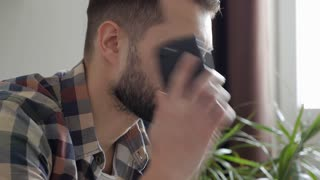 Bearded man receiving a call while working at home