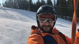 Bearded man taking selfie while sitting in a trolley chair on bright day