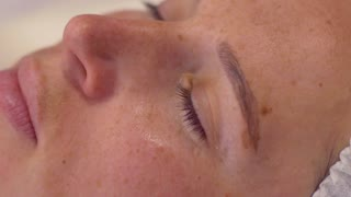 Beautician cleaning face of woman with makeup remover cloth