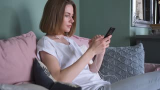 Beautiful girl with earphones relaxing on the sofa