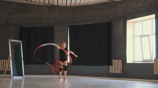 Beautiful gymnast athlete working out with art ribbon