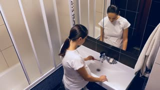 Beautiful pregnant woman brushing teeth in the bathroom