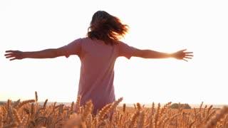 Beautiful woman spinning around in wheat field