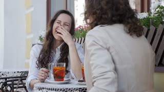 Beautiful women laughing while drinking tea at the outdoors cafe