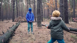 Blindfolded boy trying to catch brother in forest