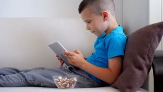 Boy absorbed by tablet playing games while sitting on sofa