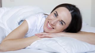 Brunette broadly smiling while hugging white pillow