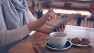 Busy mature woman working on digital, tablet in cafe