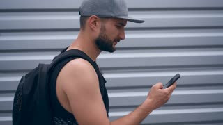 Busy modern bearded man texting on phone while walking at street
