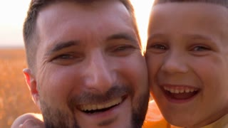 Candid father and son smiling at camera
