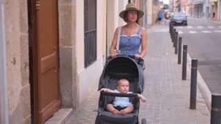 Candid woman walking with pretty baby in carriage along street