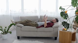 Carefree man using tablet while resting on the sofa
