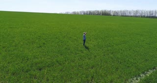 Carefree mature man with outstretched arms on green field