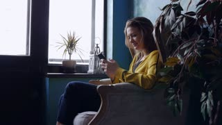 Carefree positive brunette sitting in an armchair with a smartphone