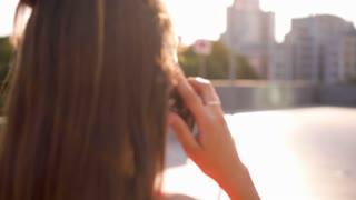 Carefree teenager talking on phone while walking on street