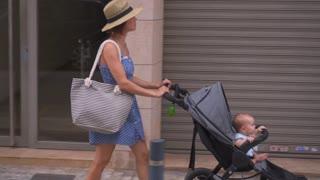 Caucasain woman with baby in stroller walking in street