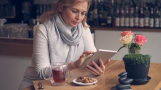 Cheerful Caucasian woman drinking tea and using tablet