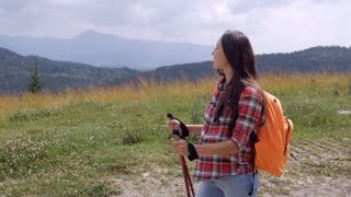 Cheerful pregnant woman hiking with poles in mountains, slow motion