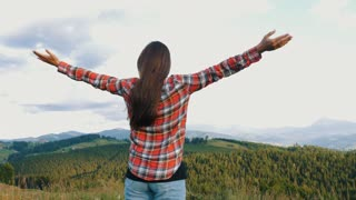 Cheerful pregnant woman with outstretched hands in mountains